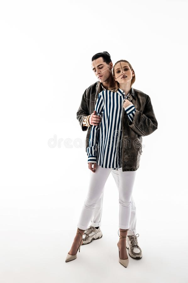 Model wearing white trousers standing near handsome colleague. Near handsome colleague. Appealing model wearing white trousers standing near handsome colleague royalty free stock photography