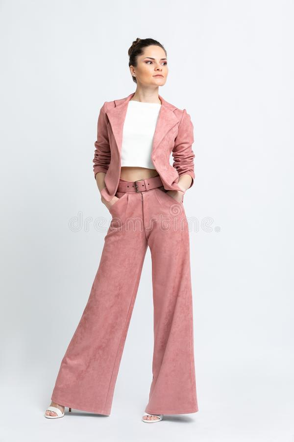 Model in white blouse, pink flared trousers with belt and jacket, white sandals with heels, with a silver chain around the neck, i. Solated on a white background royalty free stock photo