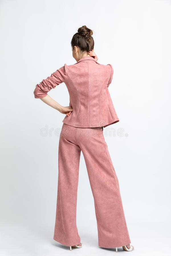 Model in white blouse, pink flared trousers with belt and jacket, white sandals with heels, with a silver chain around the neck, i. Solated on a white background stock images