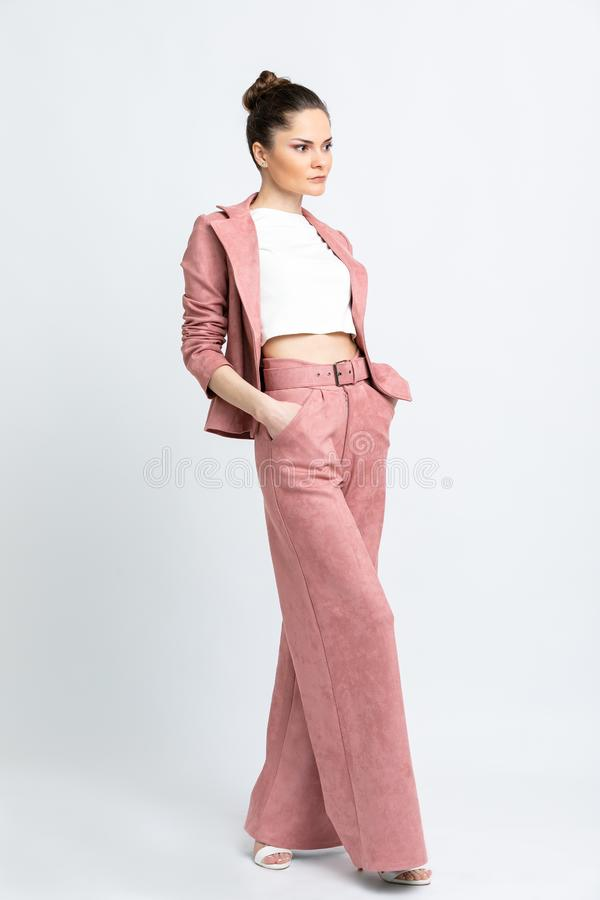 Model in white blouse, pink flared trousers with belt and jacket, white sandals with heels, with a silver chain around the neck, i. Solated on a white background royalty free stock images
