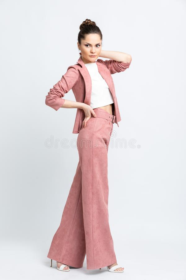 Model in white blouse, pink flared trousers with belt and jacket, white sandals with heels, with a silver chain around the neck, i. Solated on a white background stock image