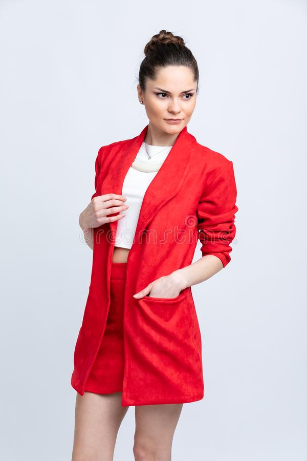 Model in white blouse, red skirt and jacket and white sandals with silver chain and pendant on neck,  on white background. stock photography