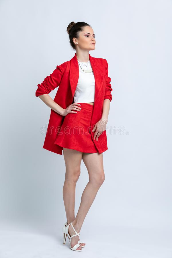 Model in white blouse, red skirt and jacket and white sandals with silver chain and pendant on neck,  on white background. stock photo