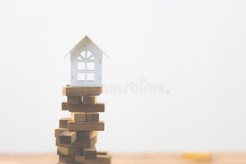 Model white house on wood block. Investment risk and uncertainty in the real estate housing market. Property investment. And house mortgage financial concept stock image