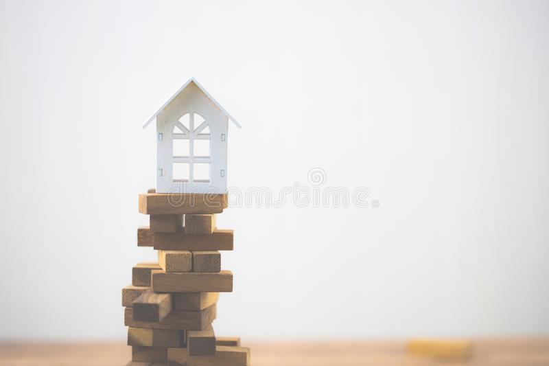 Model white house on wood block. Investment risk and uncertainty in the real estate housing market. Property investment and house mortgage financial concept stock photo
