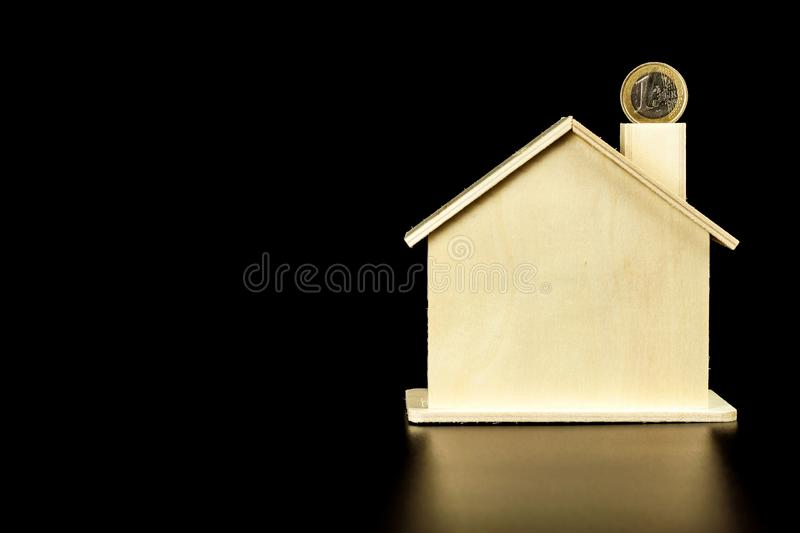 Model wooden house and Euro coin. The concept of housing finance. Bank Mortgage. Place for text. Money to build a house. royalty free stock photos