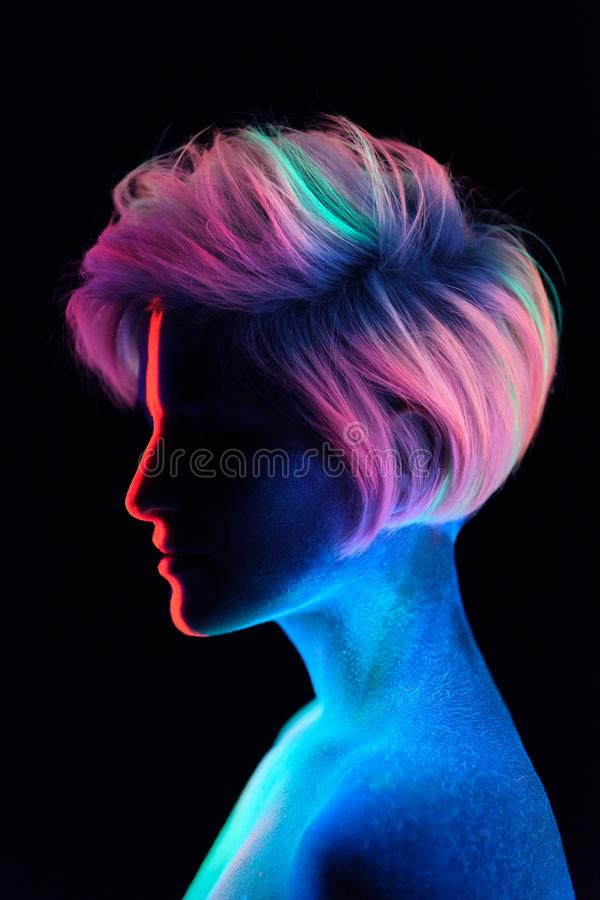 Model young beautiful girl portrait in studio with creative makeup, in neon ultraviolet lamp. Glows in the dark. Hair stock photo