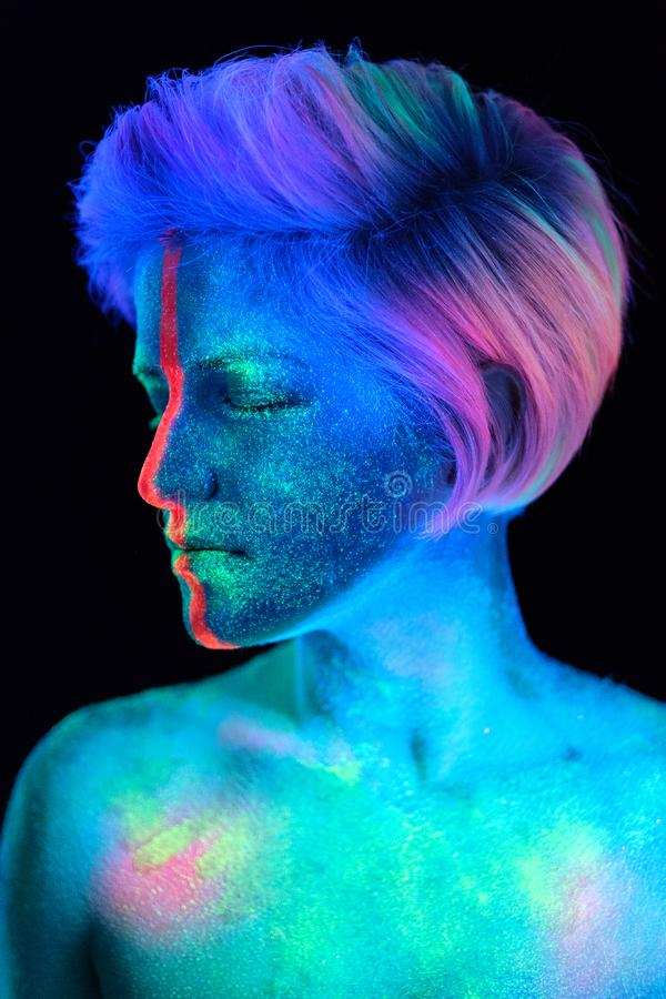 Model young beautiful girl portrait in studio with creative makeup, in neon ultraviolet lamp. Glows in the dark. Hair. Young beautiful girl model with short stock photos