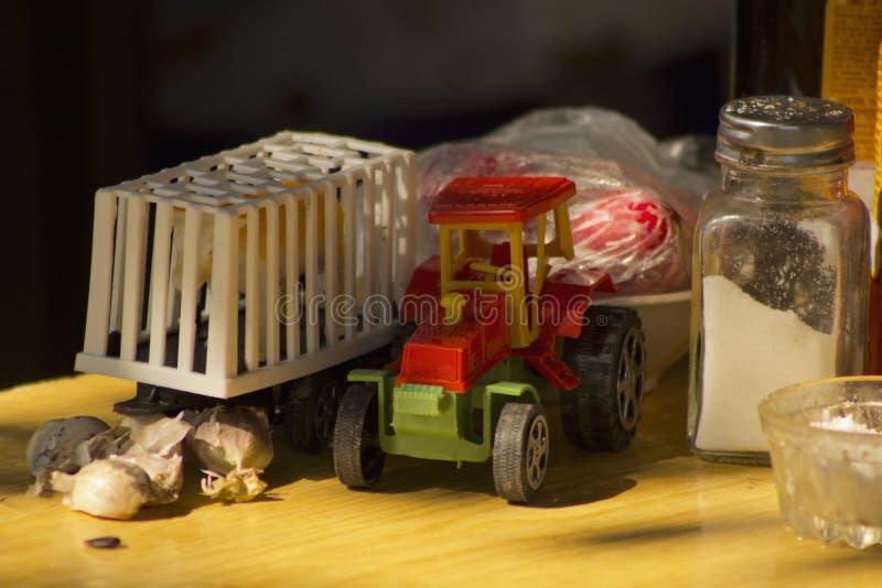 Model zabawkarski czerwony ciągnik z białą klatki przyczepą w wsi zdjęcie stock