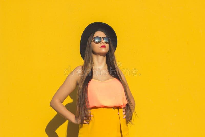 Model zich bevindt vooraan een gele muur als achtergrond stock afbeeldingen