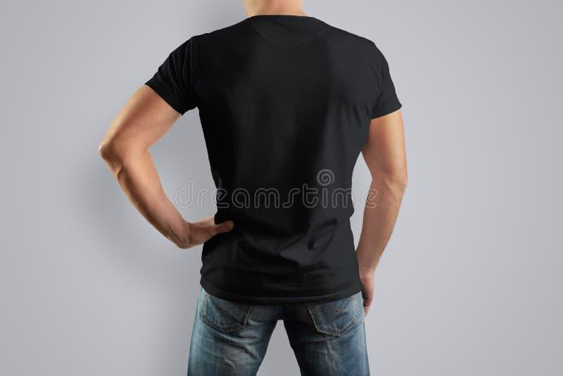 Model zwarte T-shirt op een achter sterke mens in jeans royalty-vrije stock afbeeldingen