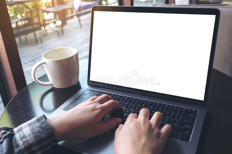 Modelbeeld van bedrijfsvrouw gebruikend en typend op laptop met lege witte het scherm en koffiekop op lijst stock afbeeldingen