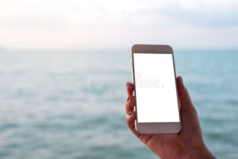 Modelbeeld van een hand die en witte mobiele telefoon met het lege zwarte Desktopscherm houden tonen voor het overzees en de blau royalty-vrije stock foto