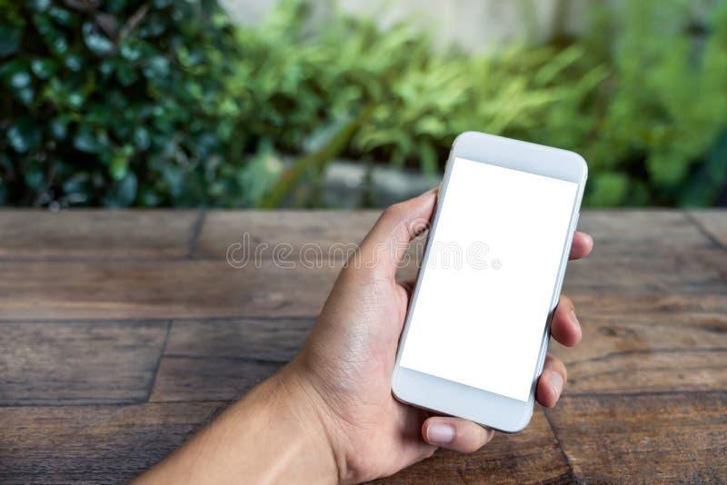 Modelbeeld van een mensen` s hand die en witte slimme telefoon met het lege scherm op houten lijst en groene aard houden met behu royalty-vrije stock afbeeldingen
