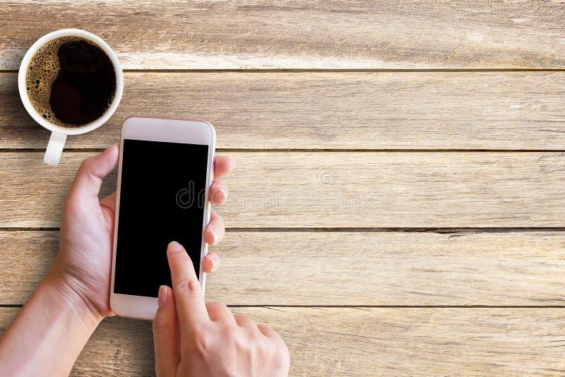 Modelbeeld van vrouwelijke hand die smartphone naast van witte kop gebruiken royalty-vrije stock afbeelding
