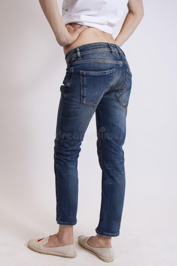Modelbenen in jeans op studioachtergrond stock fotografie