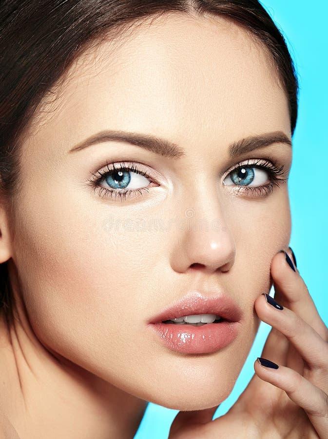 Modele com a composição do nude que toca em sua pele limpa perfeita isolada no fundo azul foto de stock