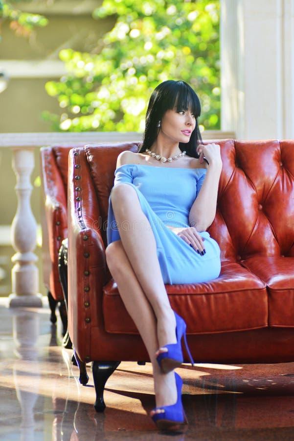 Modele em um vestido azul que levanta em um interior caro fotografia de stock