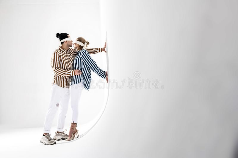 Modele jest ubranym białego trouser i pasiaste koszula pozuje blisko biel ściany obraz stock