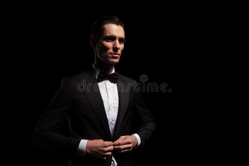 Modele no tux preto com o bowtie que levanta no estúdio escuro imagem de stock