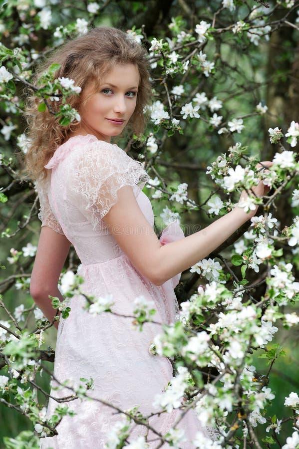 Modele no vestido cor-de-rosa que levanta nas flores brancas imagens de stock royalty free