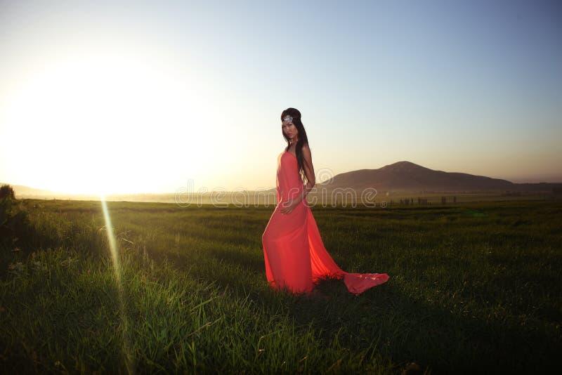 Modele no vestido vermelho que levanta no campo no por do sol fotografia de stock royalty free
