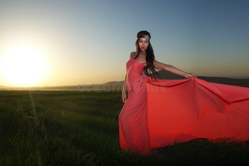 Modele no vestido vermelho que levanta no campo no por do sol imagens de stock