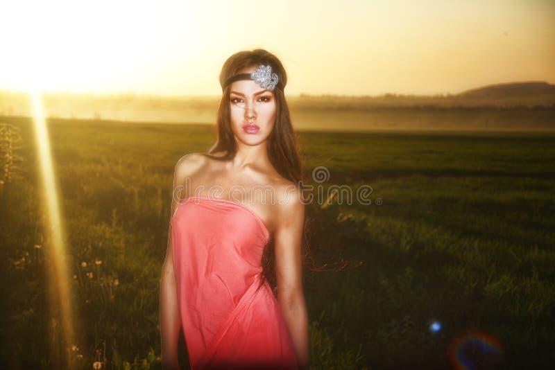 Modele no vestido vermelho que levanta no campo no por do sol foto de stock