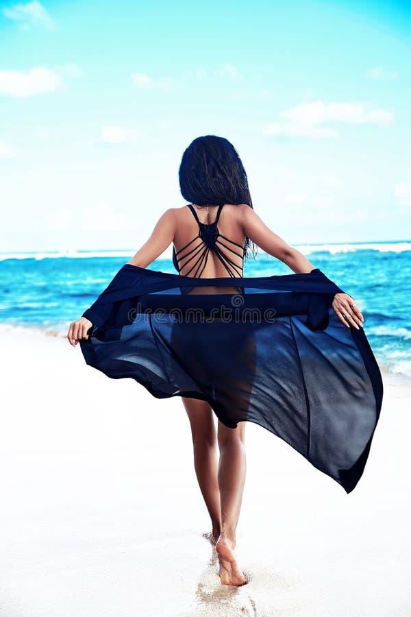 Modelez avec de longs cheveux foncés dans le maillot de bain noir avec le cap de vol posant sur la plage d'été photos libres de droits