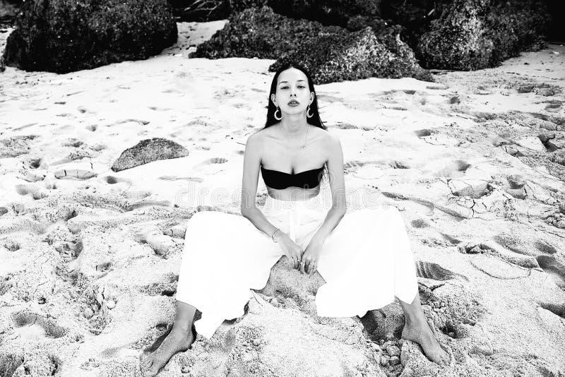 Modelez avec de longs cheveux foncés dans le pantalon classique de large-jambe sittting sur la plage d'été images libres de droits