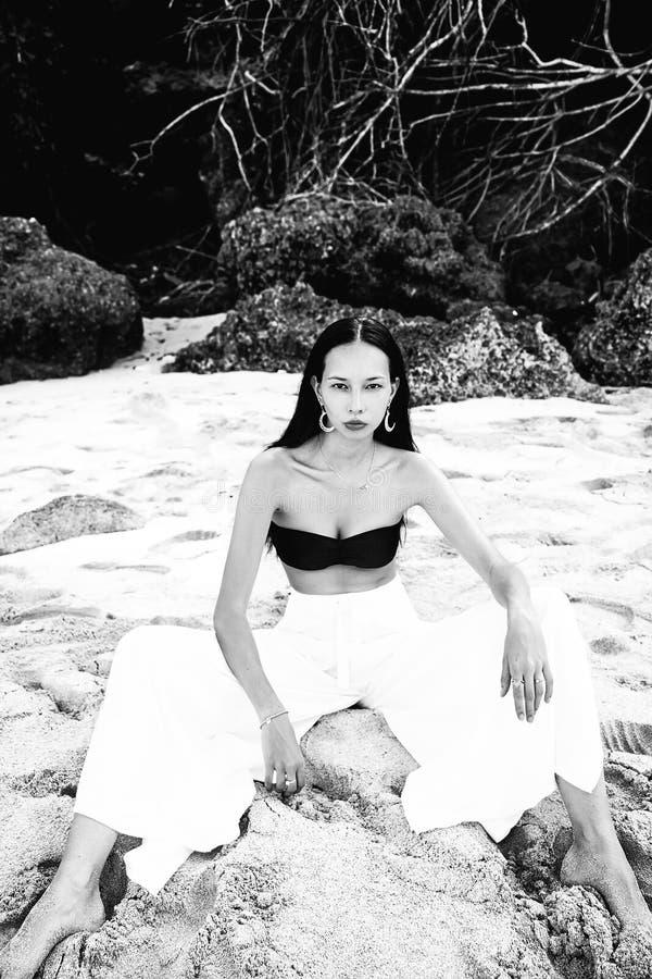 Modelez avec de longs cheveux foncés dans le pantalon classique de large-jambe sittting sur la plage d'été photographie stock