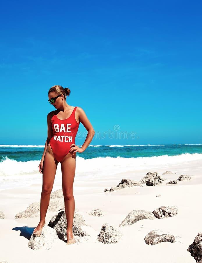 Modelez avec les cheveux foncés dans le maillot de bain rouge posant sur la plage d'été image stock