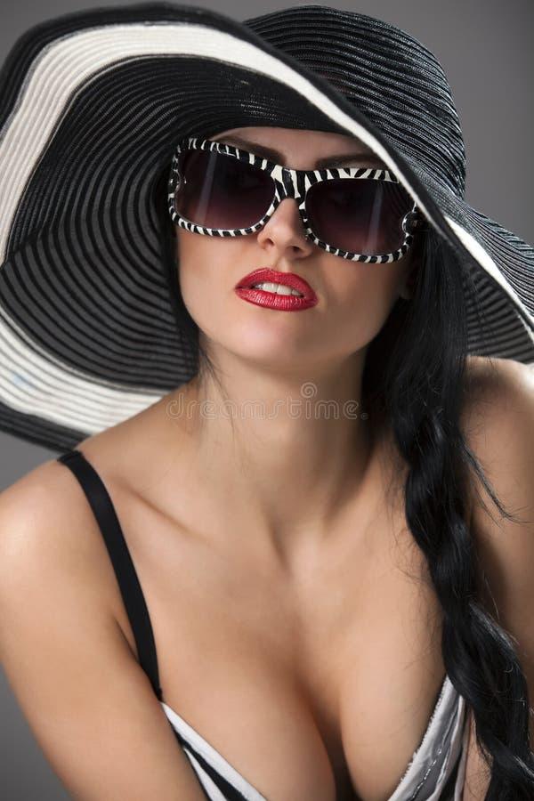 Modelez dans le chapeau et le dessus rayés avec des glassses photos libres de droits
