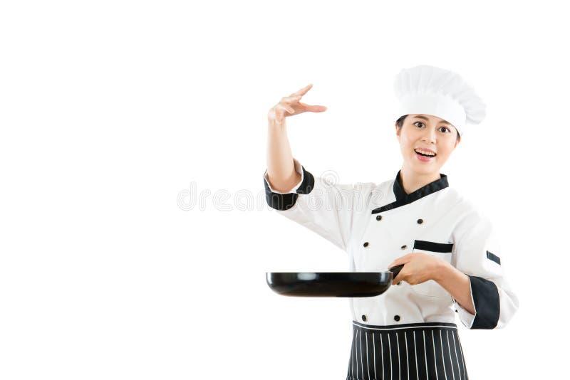 Modelholding een panshowchef-kok die zout bestrooien royalty-vrije stock afbeeldingen