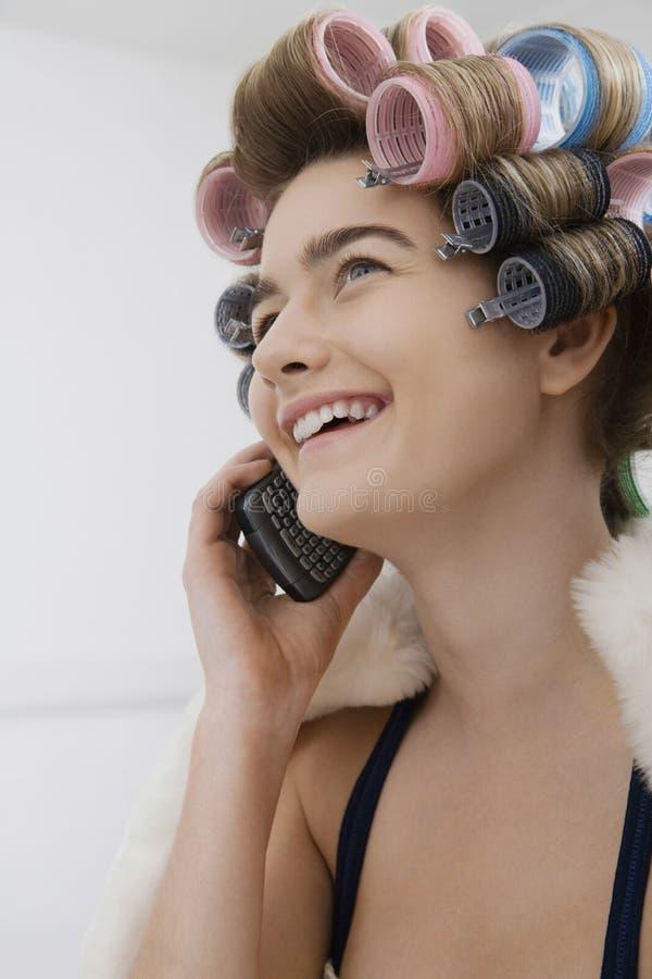 Modelin curlers talking op Cellphone stock afbeelding