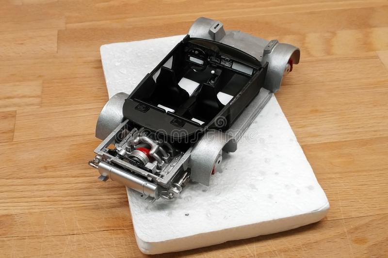 Modeling scale models. Assembling the cabin of a toy car. Installed seats, gearshift lever, dashboard. Mounted on the frame. Assembly part plastic kit assemble royalty free stock image