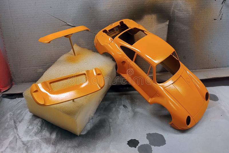Modeling scale models. Paint the spoiler, trunk lid and toy body in a bright orange color. Car sports assembly hobby plastic kit modelist vintage style brush royalty free stock photography