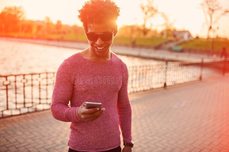 Modelivsstilbegrepp stående av den lyckliga gladlynta attraktiva svarta mannen i stilfull solglasögon som har roligt surfa royaltyfria bilder