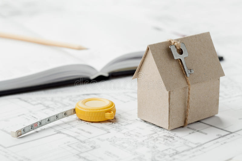 Modelkartonhuis met sleutel en meetlint op blauwdruk De huisbouw, architecturale en bouwontwerpconcept royalty-vrije stock afbeelding