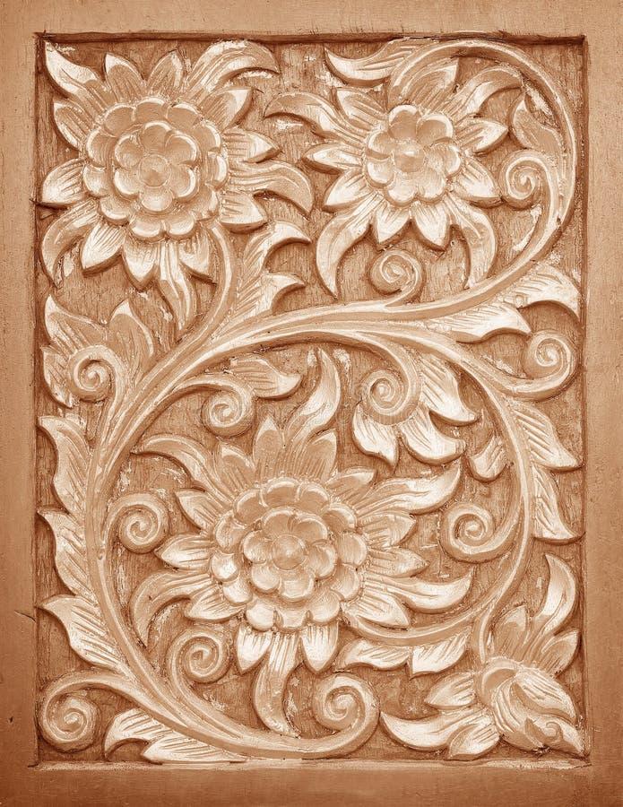 Modell av blomman som snidas på wood bakgrund arkivfoto