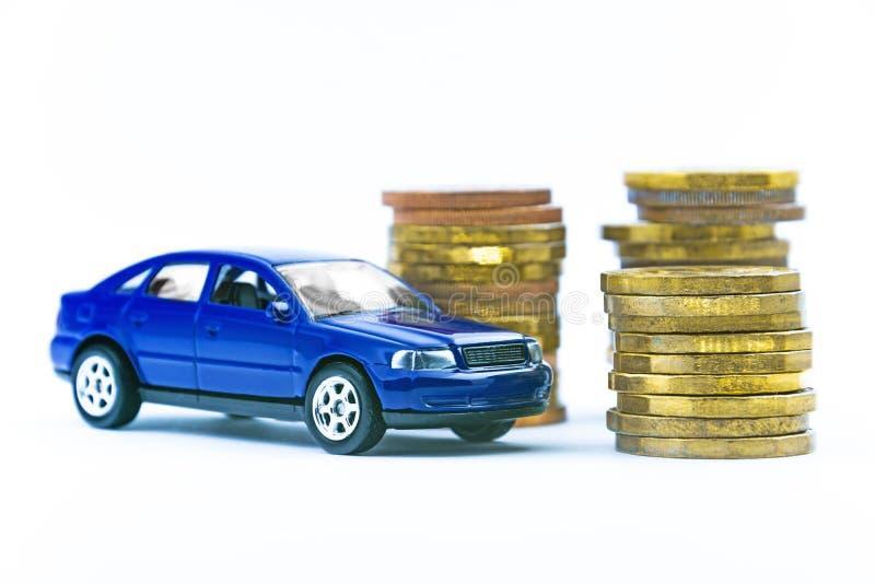 Modell av den blåa bilen och mynt på en vit bakgrund royaltyfri foto