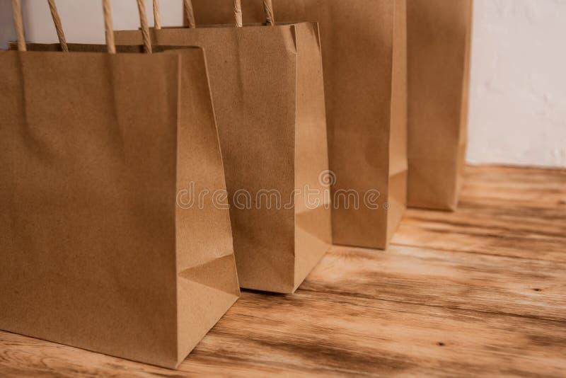 Modell av den bruna hantverkpapperspacken med handtag, den tomma shoppa påsen med område för din logo eller designen, träbräde in royaltyfria foton
