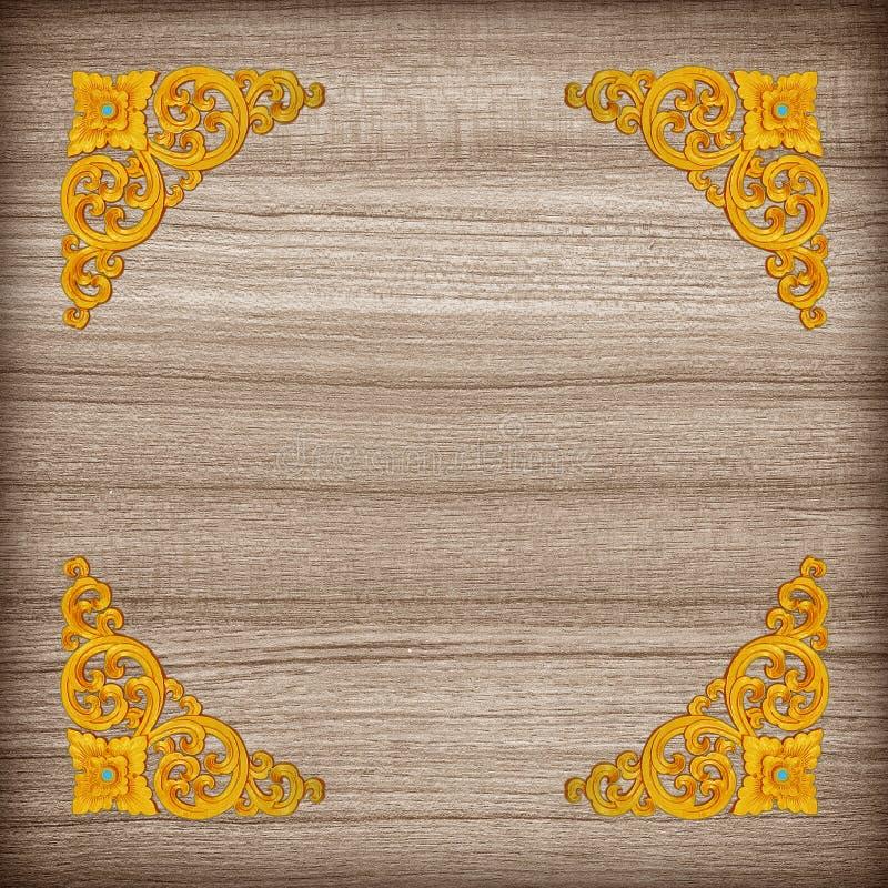 Modell av den guld- stuckaturblomman på wood bakgrund arkivfoton