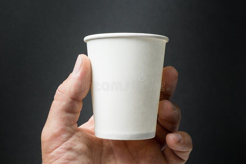 Modell av den manliga handen som kopp rymmer för ett kaffe-, te- eller fruktsaftpapper som isoleras på svart bakgrund royaltyfri foto