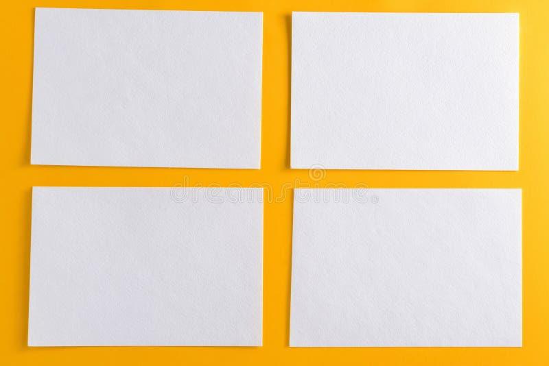 Modell av fyra vita affärskort på gul designpappersbakgrund royaltyfri foto