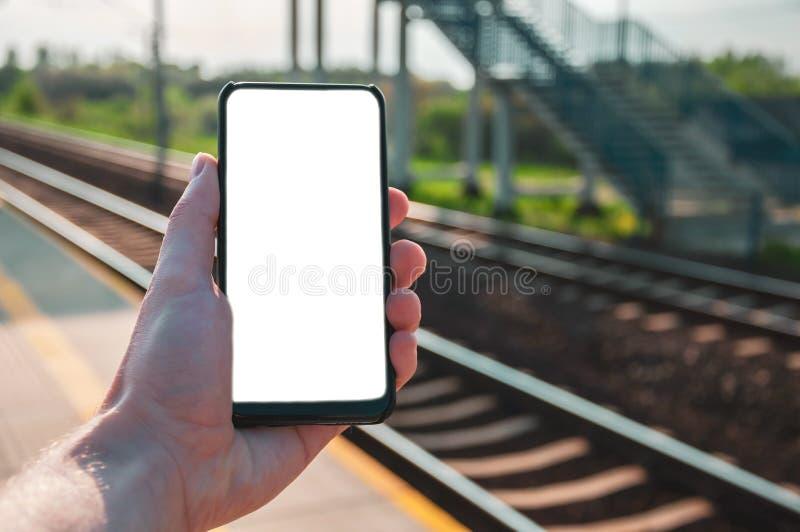 Modell av handen som rymmer en smartphone med mellanrumet, vit skärm, med järnvägsstationen i bakgrunden arkivfoto
