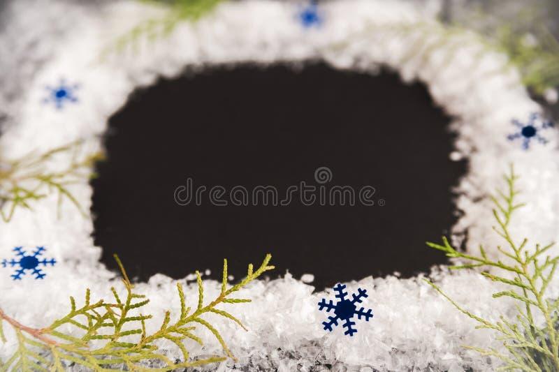 Modell av julgranfilialer och snöflingor på en svart bakgrund Begrepp för jul eller för nytt år Vinterkort arkivbild