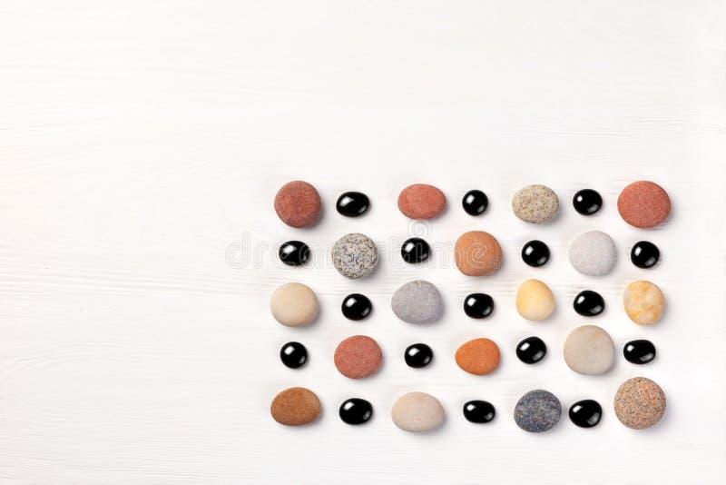 Modell av kulöra kiselstenar och svarta glass pärlor på vit träbakgrund Lekmanna- lägenhet, bästa sikt arkivbilder