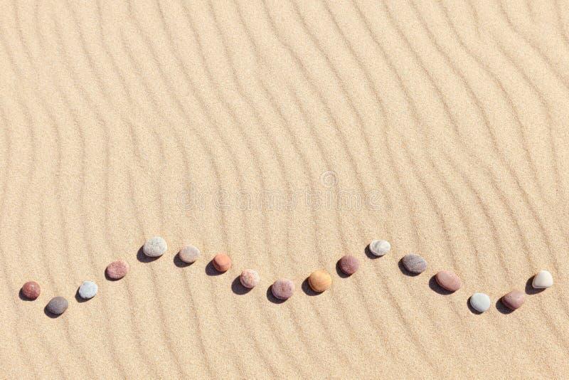Modell av kulöra kiselstenar på ren sand Zenbakgrund, harmoni och meditationbegrepp royaltyfria bilder