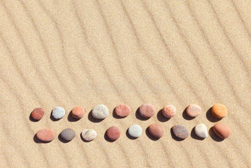 Modell av kulöra kiselstenar på ren sand Zenbakgrund, harmoni och meditationbegrepp royaltyfria foton